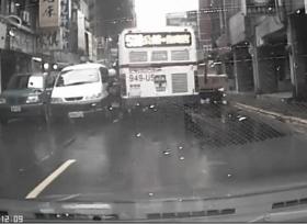 سائق دراجة نارية يعلق بين سيارة وحافلة